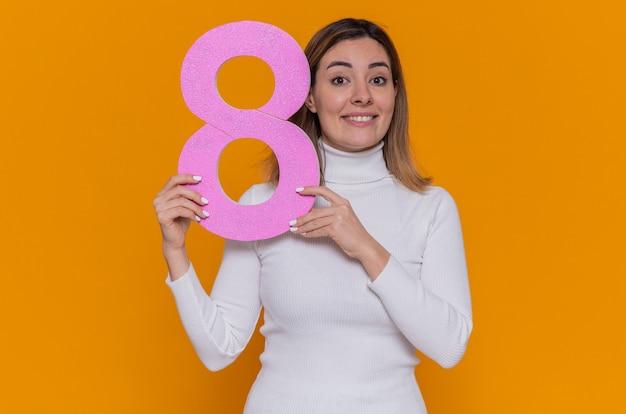 Glückliche und positive junge frau im weißen rollkragenpullover mit der nummer acht