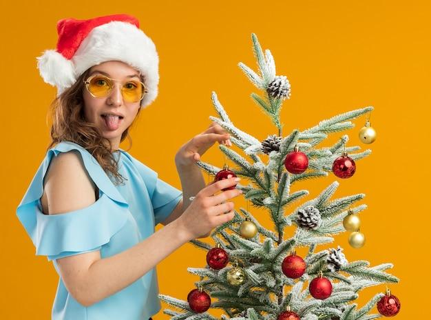 Glückliche und positive junge frau in der blauen spitze und in der weihnachtsmannmütze, die gelbe gläser tragen, die weihnachtsbaum verzieren, die herausstehende zunge betrachten kamera, die über orange hintergrund steht
