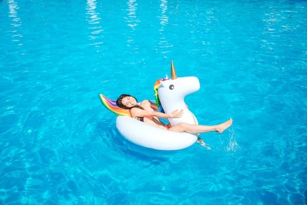 Glückliche und positive junge frau liegt auf luftmatratze mitten im schwimmbad. sie winkt mit seinem bein und lässt wasser spritzen.