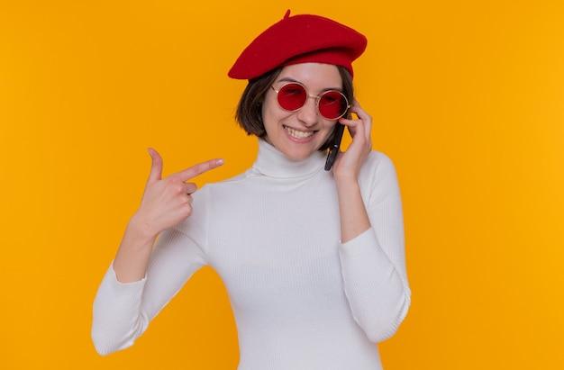 Glückliche und positive junge frau mit kurzen haaren im weißen rollkragenpullover, der baskenmütze und rote sonnenbrille trägt, die auf handy sprechen, das mit zeigefinger auf handy zeigt, das über orange wand steht