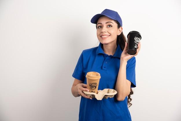 Glückliche und positive lieferfrau mit tassen kaffee.