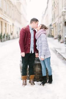 Glückliche und romantische kaukasische paare in den warmen strickjacken, die in winterstadt lemberg gehen. feiertage, winter, liebe, heiße getränke, leute