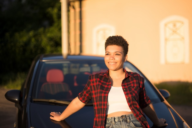 Glückliche und schöne afroamerikanerin mit kurzen haaren in der nähe des autos, lebensstil.