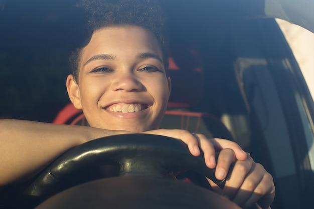 Glückliche und schöne afroamerikanerin mit kurzen haaren in einem auto, lebensstil.