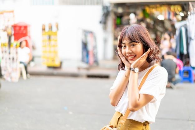 Glückliche und schöne asiatische frau, die an khao sarn road, thailand reist