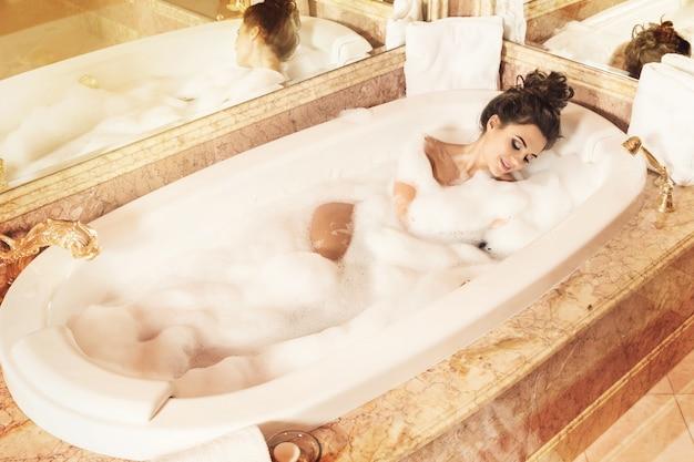 Glückliche und schöne frau nimmt bad mit einem schaum