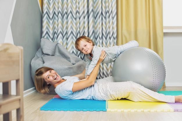 Glückliche und schöne mutter und kind, familie macht zusammen das gymnastikball-coaching