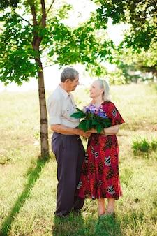 Glückliche und sehr alte paare, die in einem park an einem sonnigen tag lächeln.