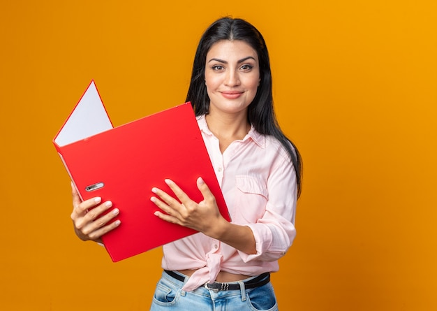 Glückliche und selbstbewusste junge schöne frau in freizeitkleidung, die einen ordner hält, der mit einem lächeln auf dem gesicht über der orangefarbenen wand steht