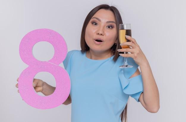 Glückliche und überraschte asiatische frau, die nummer acht und ein glas champagner hält