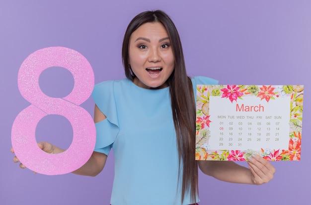 Glückliche und überraschte asiatische frau, die papierkalender und nummer acht hält