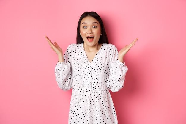 Glückliche und überraschte asiatische frau, die sich freut, die hände ausbreitet und erstaunt nach luft schnappt, mit aufregung und unglauben schaut und auf rosafarbenem hintergrund steht