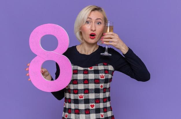 Glückliche und überraschte junge frau, die nummer acht und ein glas champagner hält, der internationalen frauenmarsch feiert