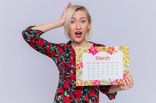 Glückliche und überraschte junge frau, die papierkalender des monatsmarsch mit hand auf ihrem kopf hält, der internationalen frauentagsmarsch feiert