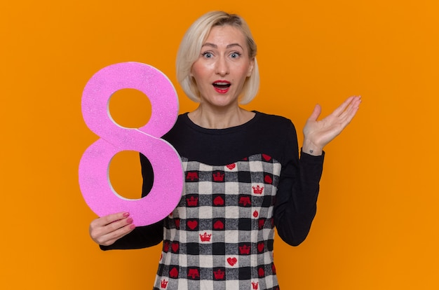 Glückliche und überraschte junge frau mit der nummer acht aus pappe
