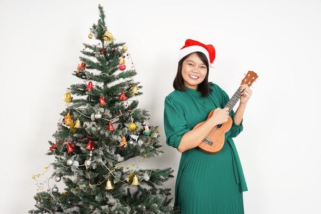 Glückliche und ukulele spielende schöne asiatische frau, die grünes kleid und weihnachtsmütze trägt