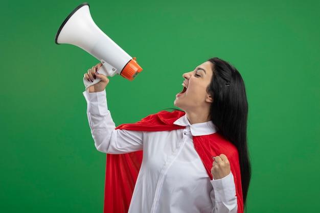 Glückliche und verrückte junge superfrau, die in der profilansicht steht und im lautsprecher schreit, der gerade auf grüner wand lokalisiert schaut