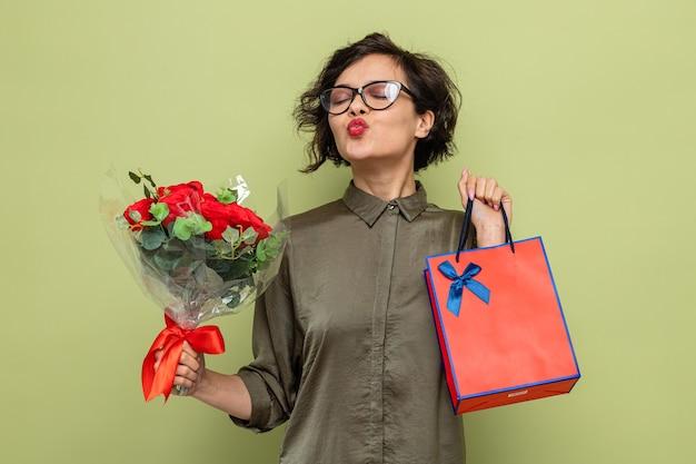 Glückliche und zufriedene frau mit kurzen haaren, die blumenstrauß und papiertüte mit geschenken hält, die die lippen halten, als würden sie küssen