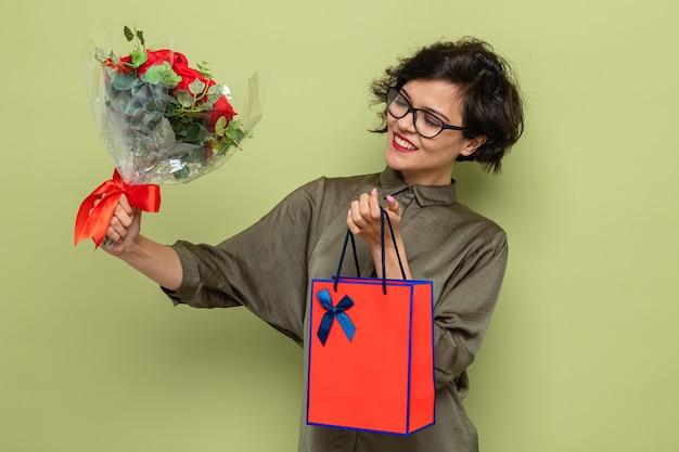 Glückliche und zufriedene frau mit kurzen haaren, die einen blumenstrauß und eine papiertüte mit geschenken hält, die fröhlich lächelt