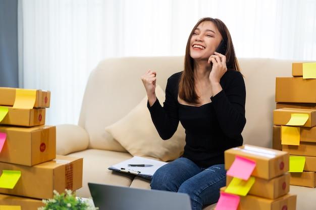 Glückliche unternehmerin, die auf einem smartphone spricht und laptop-computer verwendet, um produkt online zu hause zu verkaufen