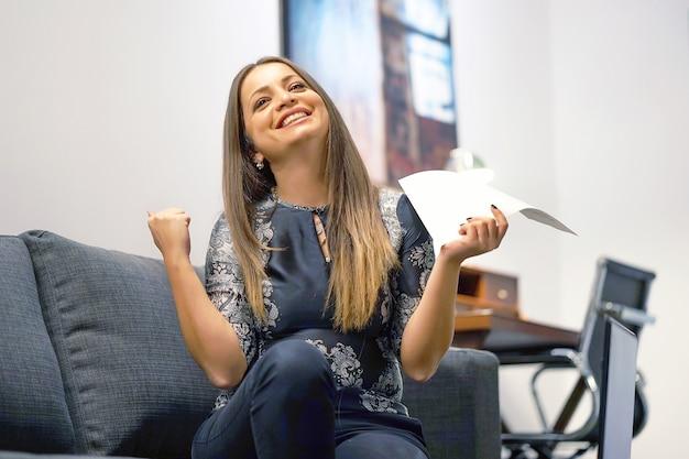 Glückliche unternehmerin, die gute nachrichten in einem brief auf sofa liest