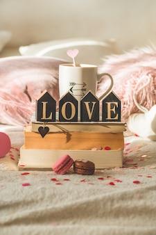 Glückliche valentinstagpostkarte. liebeskonzept für muttertag und valentinstag. herzen und die bücher mit tasse kaffee. valentinskarte mit platz für text