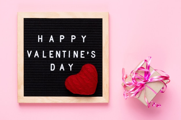 Glückliche valentinstagwörter auf schwarzem briefbrett