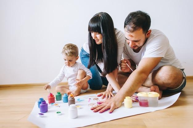 Glückliche vatermutter- und -sohnshowhände der freudenfamilienkunst glückliche in den hellen farben malen zusammen bildkunst