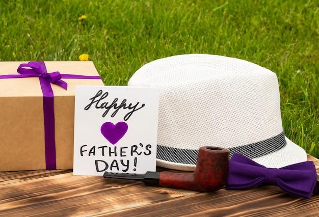 Glückliche vatertagskarte mit geschenk, box-krawatte, handgelenk, hut und pfeife auf holz- und grashintergrund