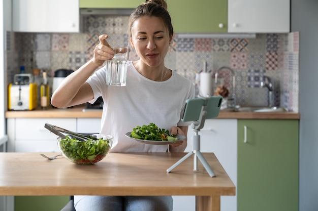 Glückliche vegane frau, die glas wasser im video-chat zu hause küche zeigt, bereitete gesunden salat vor. diät.