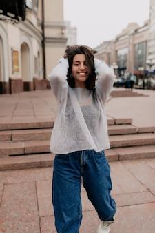 Glückliche verlassene frau mit langen haaren, die blauen pullover und jeans tragen, die auf stadthintergrund gehen und lächeln. attraktives fröhliches mädchen gehen glücklich