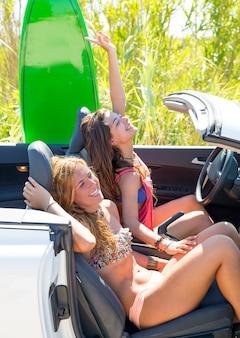 Glückliche verrückte jugendlich surfermädchen, die auf auto lächeln