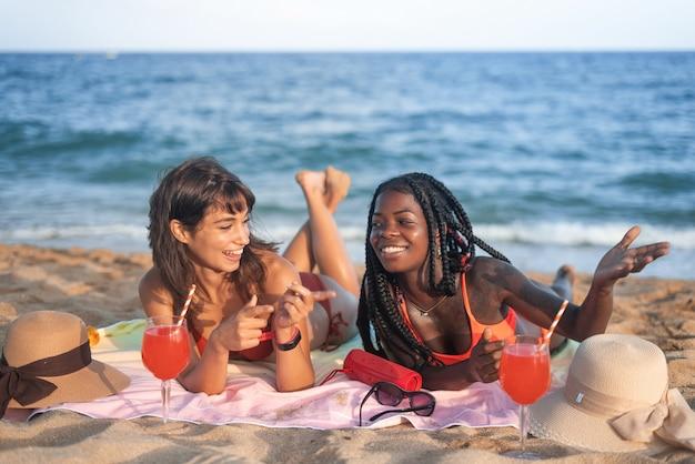 Glückliche verschiedene freundinnen, die am strand chillen