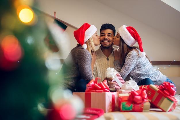 Glückliche verspielte reizende weihnachtsfreunde mit weihnachtsmützen und pullovern, die haus für feiertage genießen.