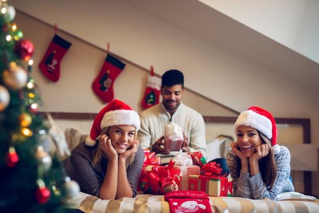 Glückliche verspielte schöne weihnachtsfreunde mit weihnachtsmützen und pullovern