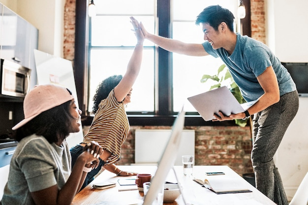 Glückliche, vielfältige kollegen in einem startup-unternehmen, die ein high five machen