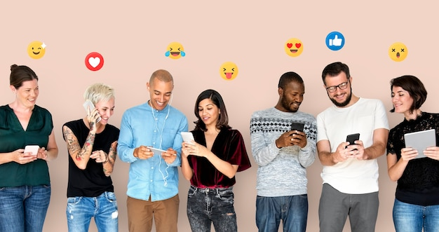 Glückliche, vielfältige menschen, die digitale geräte verwenden