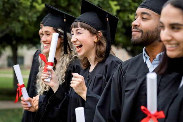Glückliche, vielfältige studenten, die die universität abschließen und mit diplomen feiern