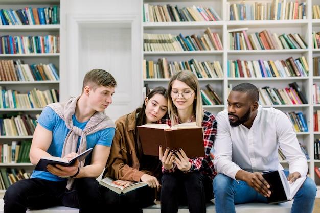 Glückliche vier junge universitätsstudenten, die mit büchern in der bibliothek studieren