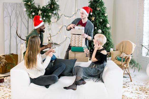 Glückliche vier multiethnische freunde, die weihnachtsgeschenke teilen