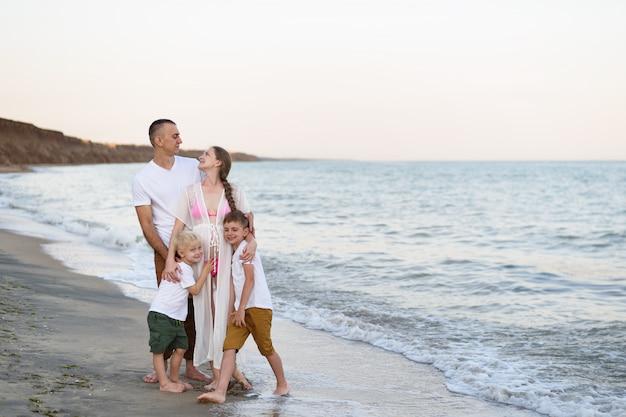 Glückliche vierköpfige familie, die auf der seeküste umarmt. eltern, schwangere mutter und zwei söhne.