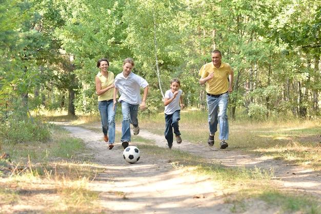 Glückliche vierköpfige familie, die fußball im wald spielt