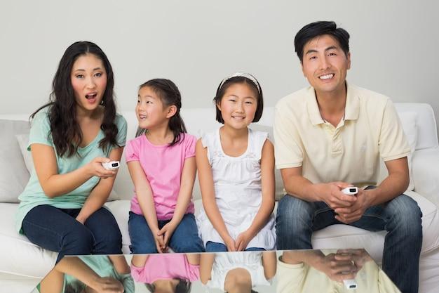 Glückliche vierköpfige familie, die im wohnzimmer fernsieht