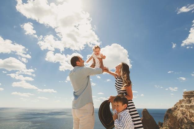 Glückliche vierköpfige familie, die in den bergen geht. vater wirft tochter in den himmel.