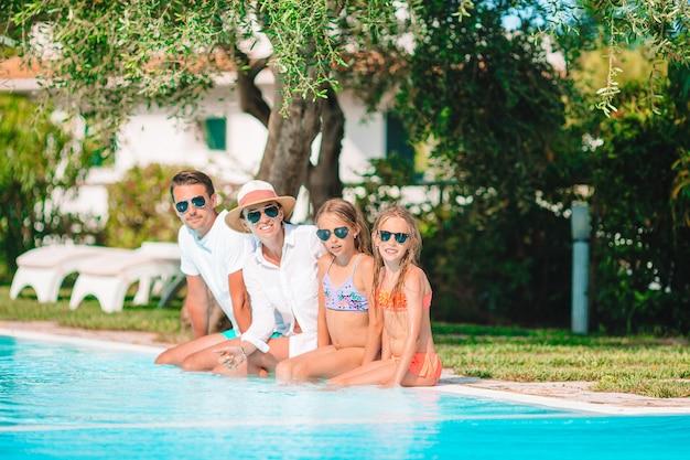 Glückliche vierköpfige familie im swimmingpool
