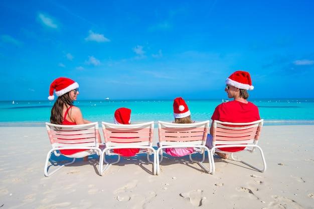 Glückliche vierköpfige familie in santa hat auf sommerferien