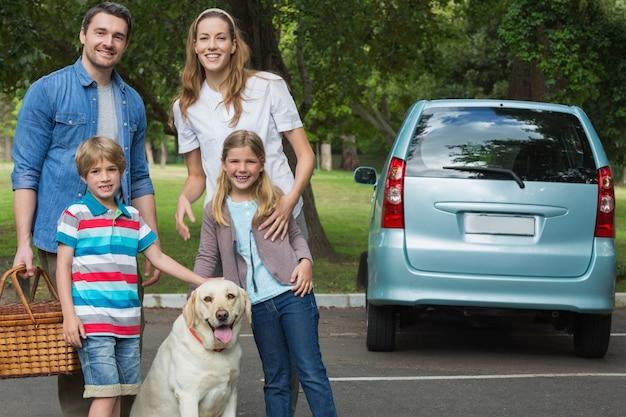Glückliche vierköpfige familie mit auto am picknick