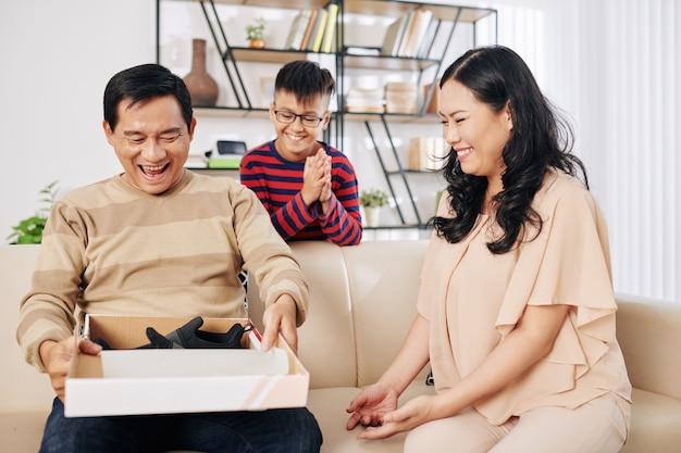 Glückliche vietnamesische mutter und sohn betrachten vater, der geschenkbox mit neuen schuhen öffnet, die sie ihm zum geburtstag gaben