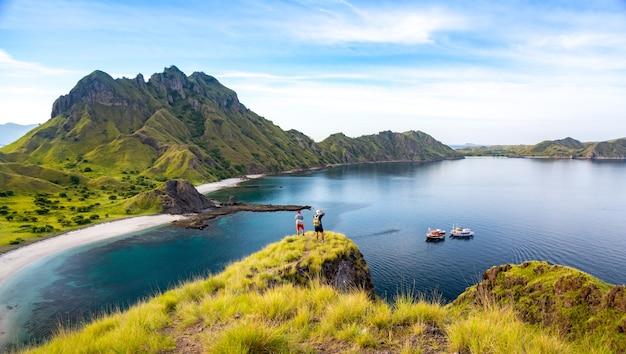 Glückliche wanderer, die auf klippen-berg stehen, genießen die ansicht von padar island vor sonnenuntergang bei k