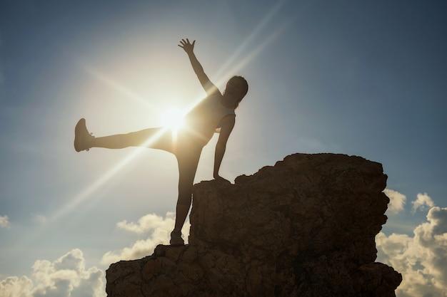 Glückliche wandernde frauenerhöhungshand und -bein des schattenbildes nachdem dem erreichen der spitze des hügels mit sonnenuntergang